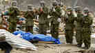 Members of Japan Self-Defense Force pray for the body of a tsunami victim wrapped in a tarp in Onagawa, Miyagi Prefecture.
