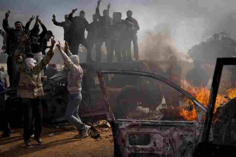 Libyan rebels celebrate next to burning cars after Libyan leader Moammar Gadhafi's forces where pushed back from Benghazi, eastern Libya.