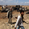 Libyan rebels walk past the wreckage of military vehicles belonging to Gadhafi forces bombed by the French airplanes in al-Wayfiyah west of Benghazi.