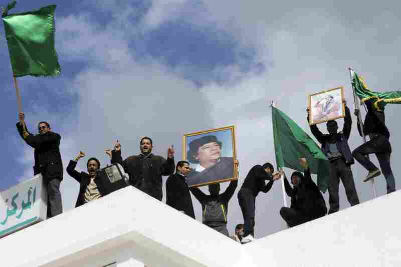 Pro-Gadhafi supporters in Tunisia rally on the roof of the Libyan Cultural Center.