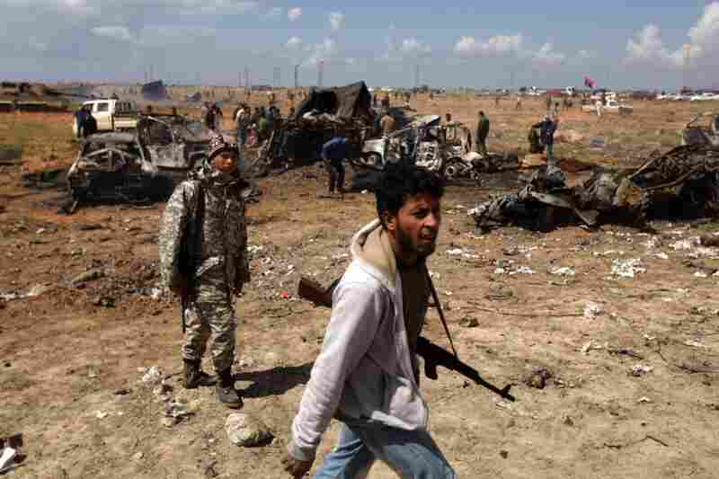 Libyan rebels walk past the wreckage of military vehicles belonging to Gadhafi forces bombed by French airplanes in al-Wayfiyah, west of Benghazi.