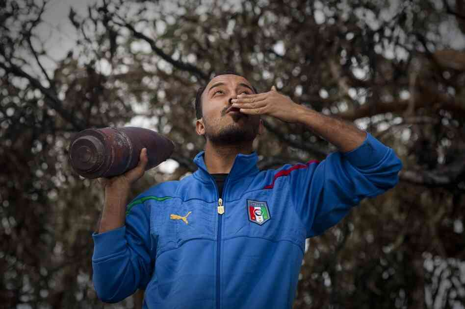 A rebel dressed in an Italian national soccer team jacket celebrates with a rocket in the outskirts of Benghazi.