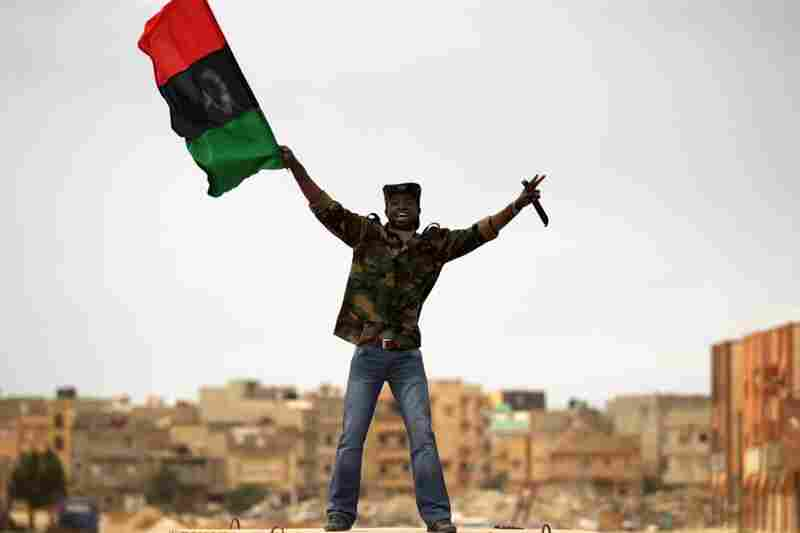 A rebel fighter waves a flag as civilians begin to flee shortly after airstrikes hit Benghazi.