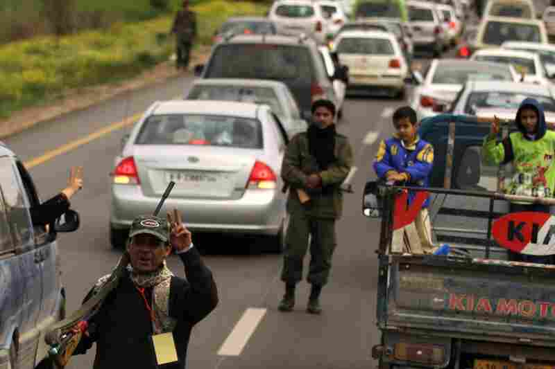 Rebel fighters direct a traffic of people fleeing from the city from Benghazi in the town of al-Marej.