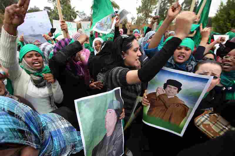 """Demonstrators in Tripoli hold pictures of Gadhafi during a protest against the U.N. no-fly resolution. The resolution authorizes """"all necessary measures"""" to protect Libyan civillans."""