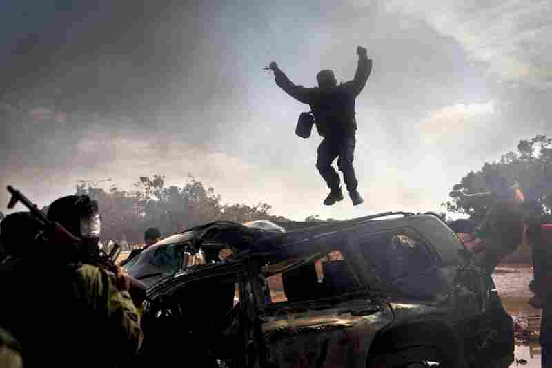 A rebel jumps on top of a burning car after Gadhafi's forces are pushed back from Benghazi.