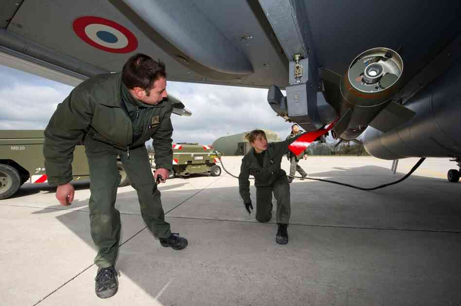 Soldiers prepare a jet fighter at the military base of Saint Dizier, eastern France, on Saturday.