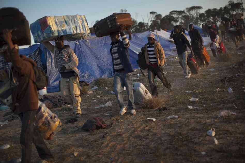 Workers fleeing the unrest in Libya arrive at a refugee camp at the Tunisia-Libyan border.