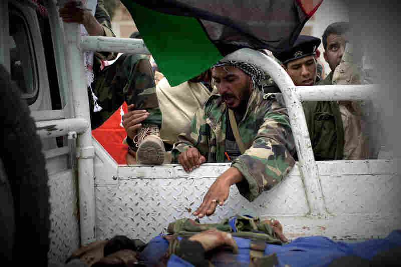 A Libyan rebel reaches out to touch the hand of a dead comrade before the man and another killed rebel are driven away from the front line near Sultan, south of Benghazi, on Friday.