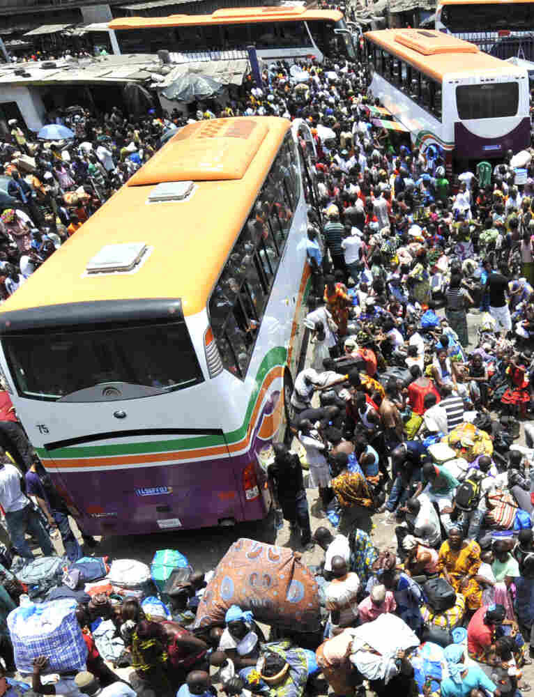 Residents of Abidjan wait for buses Saturday to flee increasing violence in Ivory Coast.