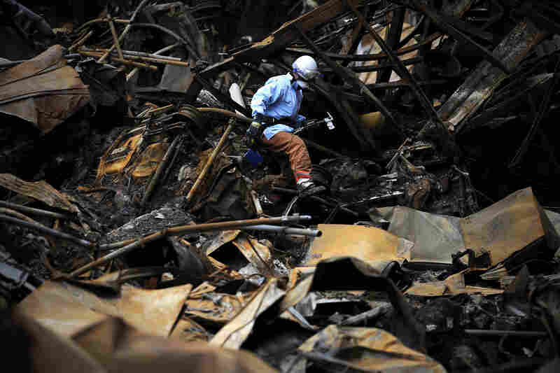 A Japanese fireman searches for bodies in the rubble in Minamisanriku.  Miyagi prefecture was worst hit by the quake and tsunami, with a confirmed death toll of 4,882 so far.