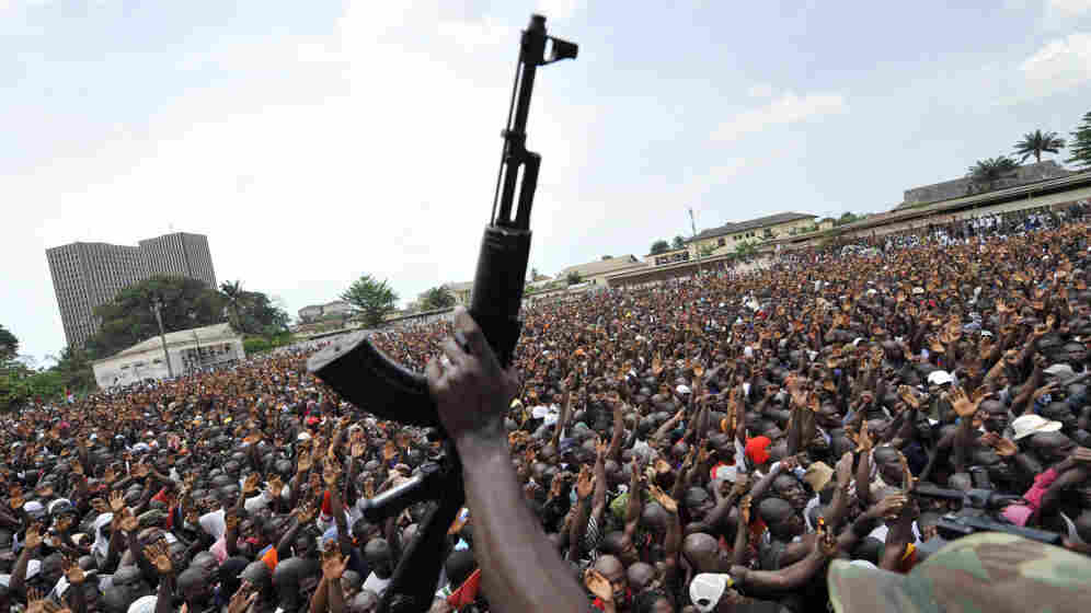 An Ivorian soldier brandishes his gun Monday in front of thousands of young supporters of disputed President Laurent Gbagbo who gathered in Abidjan to enlist in the army.