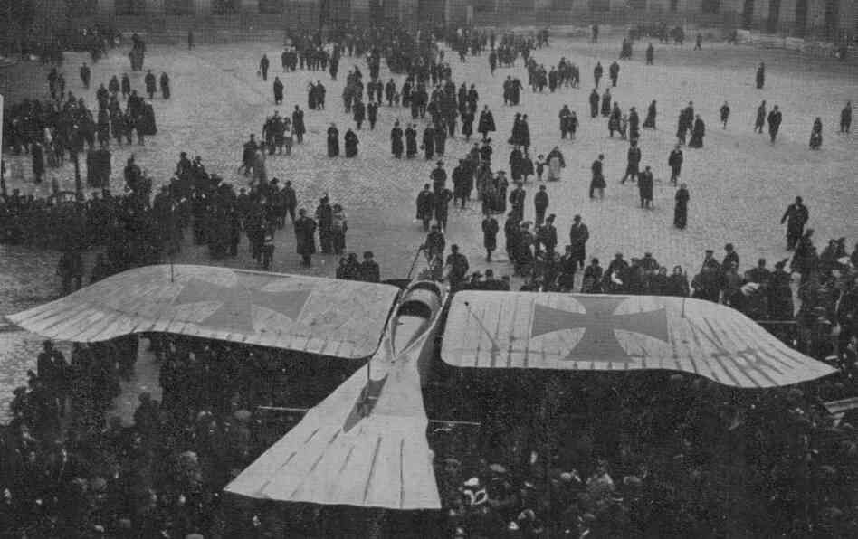 circa 1915:  Crowds gather to see a birdlike German 'Taube' aircraft, on display at Les Invalides, Paris, at the height of the First World War.