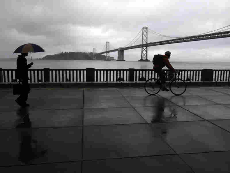 A pedestrian and cyclist are seen along the Embarcadero with the San Francisco Oakland Bay Bridge in the background. San Francisco dismantled a freeway in this location in the early 1990s.