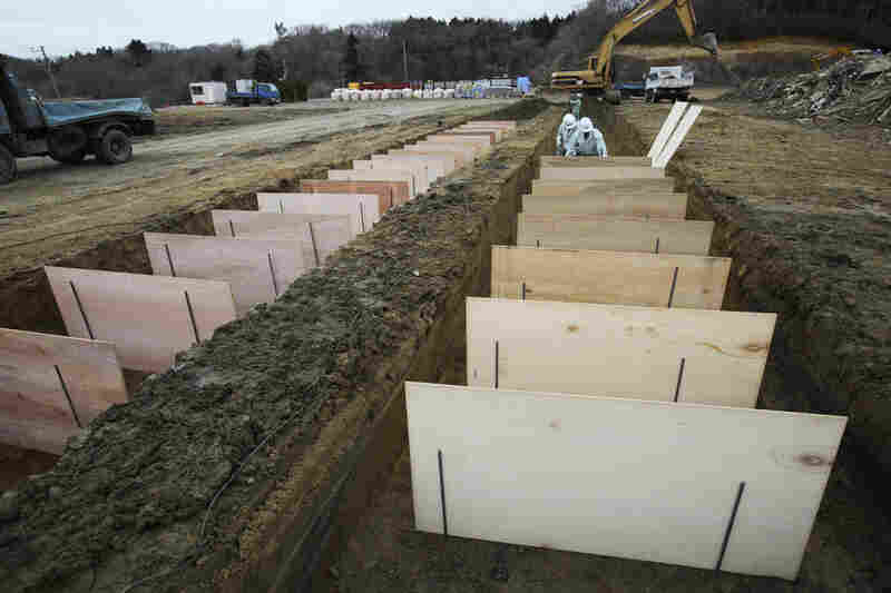 Workers prepare for a mass burial planned for Tuesday in Higashimatsushima city.