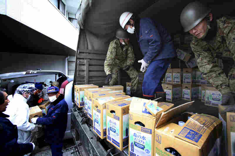 Japanese soldiers unload boxes of drinking water from a truck as relief supplies arrive in Iitate, Fukushima prefecture. The Health Ministry advised residents not to drink tap water because of elevated iodine levels.