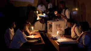 "Electoral workers count ballots by candlelight at a polling station at the end of a presidential runoff in Port-au-Prince, Haiti, on Sunday. The two choices were Mirlande Manigat, the former first lady, and Michel ""Sweet Micky"" Martelly, a Haitian music star. Results are expected at the end of March."