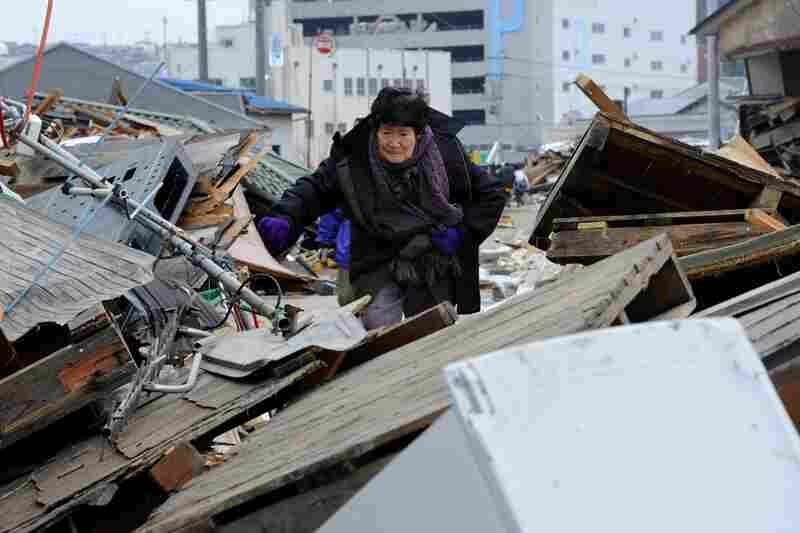 A woman makes her way through piles of debris in Ishinomaki, Miyagi prefecture.