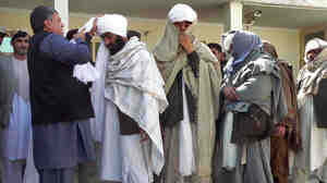Kandahar Gov. Tooryalai Wesa, left, puts a turban on former Taliban fighter Malawi Azizullah.