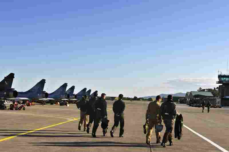 French pilots walk on the tarmac at Solenzara Air Base after a mission to Libya on Sunday. France sent about 15 planes to eastern Libya.