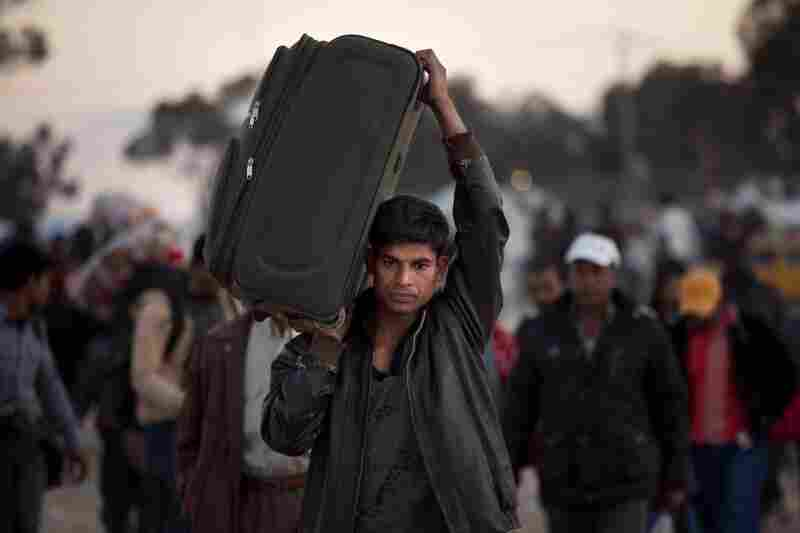 A man from Bangladesh, who used to work in Libya and fled the unrest in the country, carries his belongings Monday as he arrives at a refugee camp on the Tunisia-Libyan border, in Ras Ajdir, Tunisia.