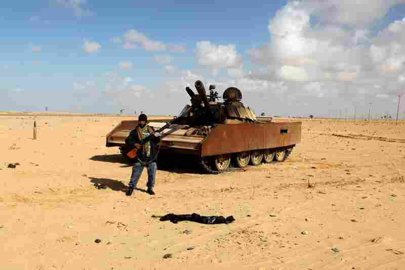 A rebel walks past a wrecked T-55 tank belonging to the forces of Gadhafi in Shat al-Bedin, about 31 miles west of Benghazi.