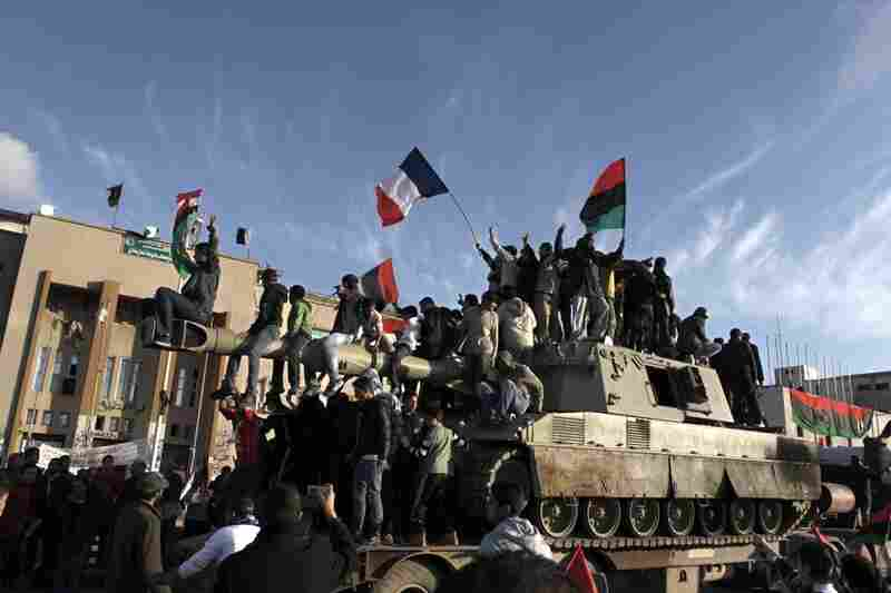 Libyans wave the French flag as they parade on a 155mm Howitzer belonging to Gadhafi forces in the eastern rebel-held city of Benghazi.