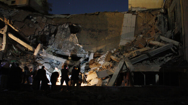 People stand near the rubble of Libyan government building destroyed by an Allied air strike on March 20, 2011.