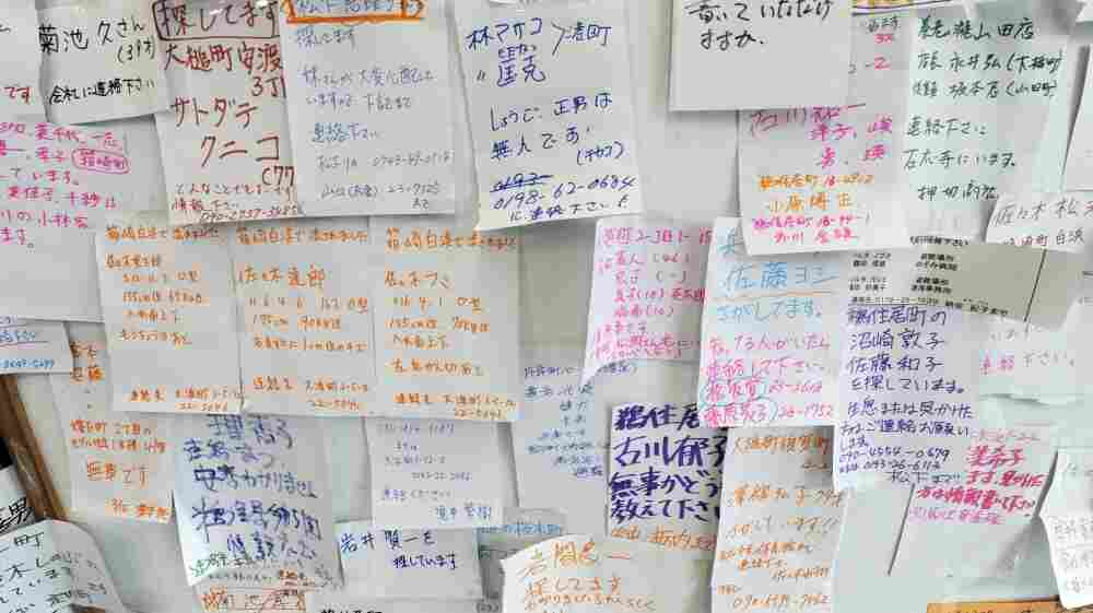 Notes of survivors looking for missing family members are posted on a board at the reporting center in Kamaishi.