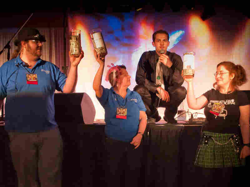 """Zenkaikon staff members Brian Harkless (left), Colette Fozard and Matilda  Madden (right), collecting donations for Japanese tsunami victims. Comedian Karl  """"Uncle Yo"""" Custer emcees at center."""