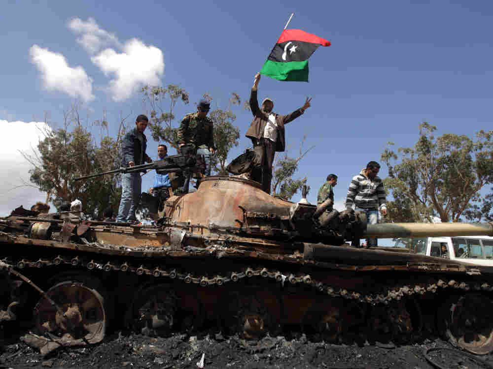 Libyan rebels wave their flag on top of a damaged tank belonging to Libyan government forces, at the western entrance of Benghazi.