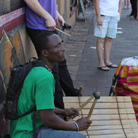 Percussionists Gidi Agbeko (green shirt) and Sam Bathrick (purple shirt) play on the street at SXSW in Austin on March 18, 2011.