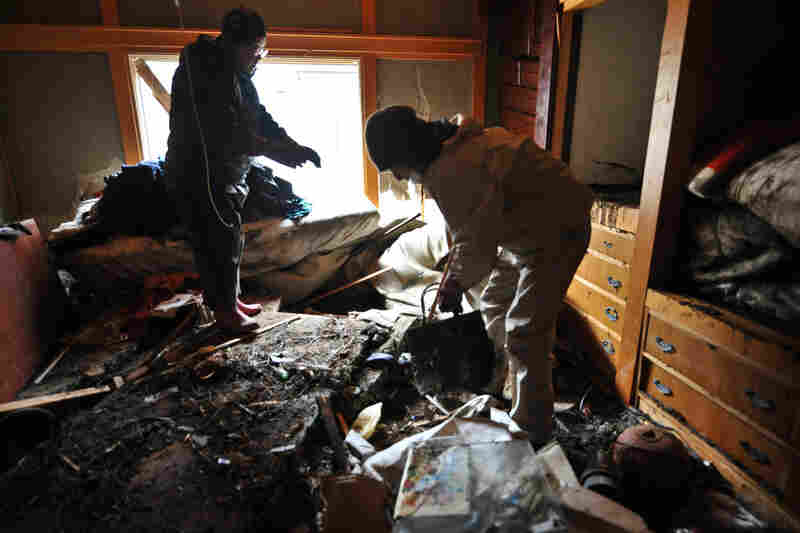 A man and his son clean up their house in the devastated city of Ishinomaki.