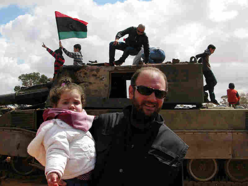 Ahmed Jarbou, 45, a businessman from Benghazi, and his 2-year-old daughter, Jude, examine remnants of destroyed mobile artillery from pro-Gadhafi forces.