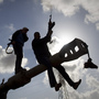 A Libyan rebel shoots in the air Sunday as he celebrates with others on a tank belonging to forces loyal to leader Moammar Gadhafi, on the outskirts of Benghazi, eastern Libya.