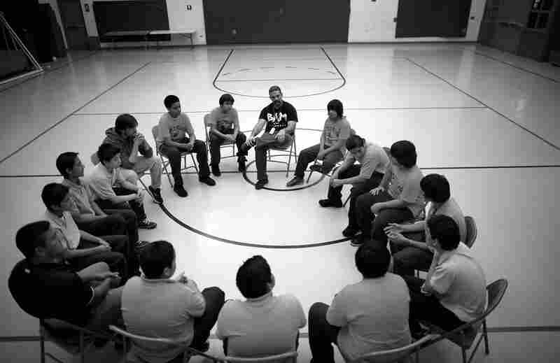 Participants in the Becoming a Man (BAM) program gather for a session in the gym at Little Village Academy in Chicago. BAM focuses on mentoring at-risk boys to prevent them from turning to violent crime.