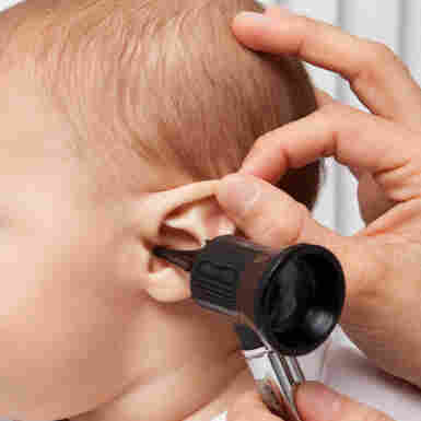 An infant gets an ear checked.