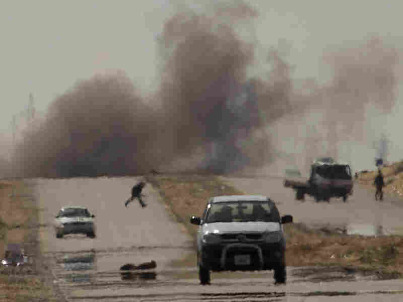 Libyan rebels try to take cover as mortars from Moammar Gadhafi's forces are fired on them on the outskirts of Ajdabiya, eastern Libya, on Tuesday.