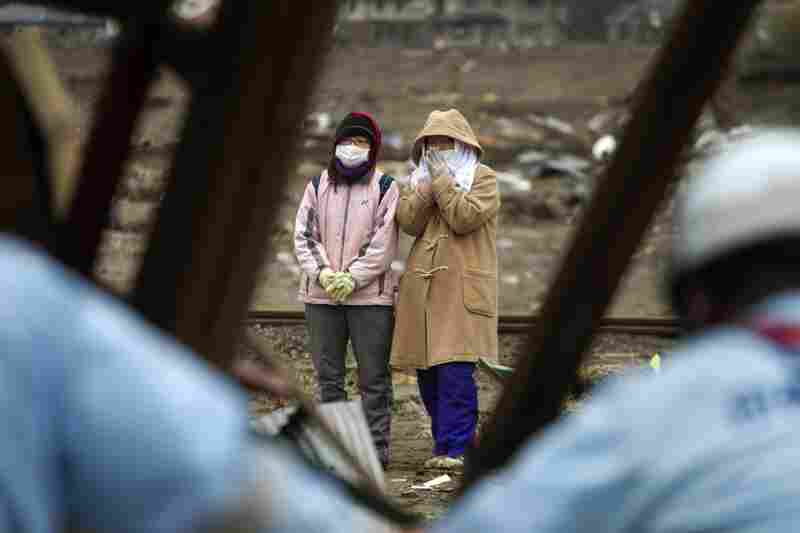 Japanese women watch recovery teams search their home in Rikuzentakata.