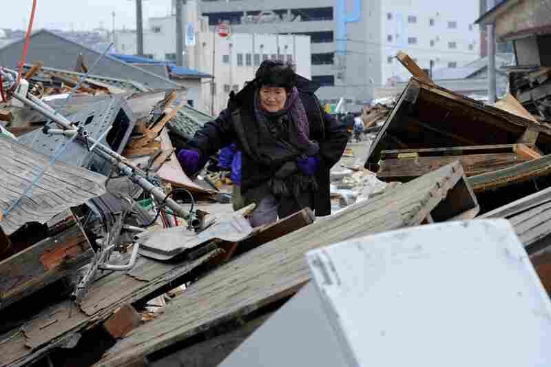 A woman makes her way through piles of debris in Ishinomaki, Miyagi prefecture.