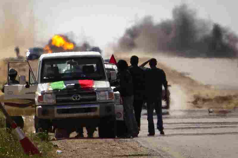 Libyan rebels stop on the road as mortars from Gadhafi's forces are fired on them outside Ajdabiya.