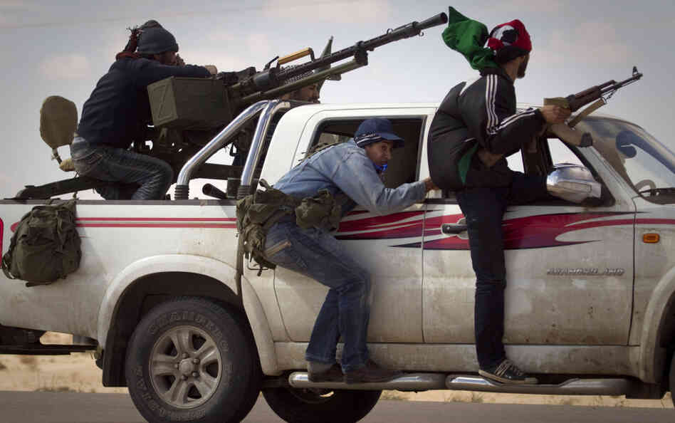 Libyan rebels retreat as mortars from Moammar Gadhafi's forces are fired on them outside Ajdabiya, south of Benghazi, Tuesday, March 22, 2011.