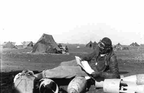 A 99th Fighter Squadron pilot studies his map  before going out on a mission during World War II, 1943.
