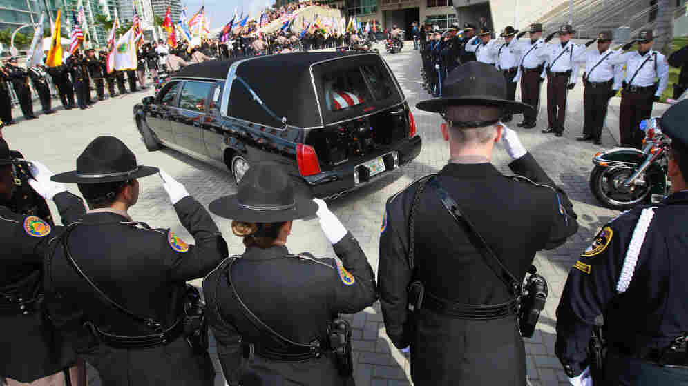 Police officers salute as a hearse carrying the body of one of two slain Miami-Dade police officers arrives for a memorial service in Miami in January. Officers Amanda Haworth and Roger Castillo were killed while serving an arrest warrant.