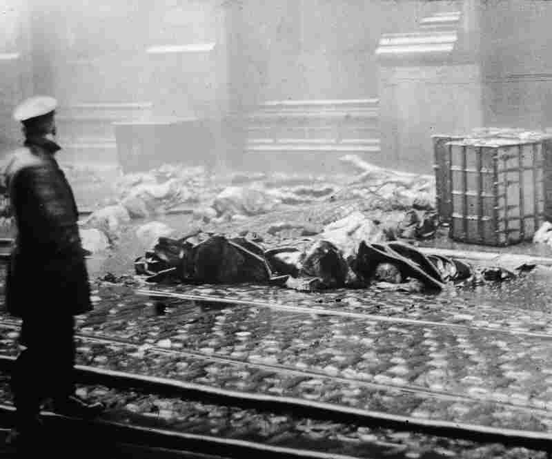 The Aftermath: A policeman stands in the street below the factory after the fire. The tragedy led to legislative reforms on a national level and spurred support for organized labor.