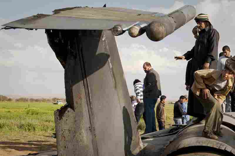 Libyans inspect the wreckage of a US  F-15 fighter jet after it crashed in an open field 25 miles southwest of the eastern rebel stronghold of Benghazi, Libya's second-largest city.