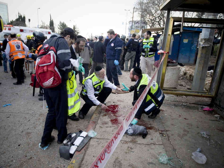 Israeli rescue workers and paramedics cleaned a pool of blood at the bus stop in Jerusalem after today's attack. (March 23, 2011).