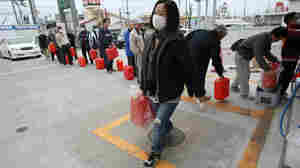 A woman carries fuel as lines of people wait with hopes of filling containers in Fukushima city on March 20.