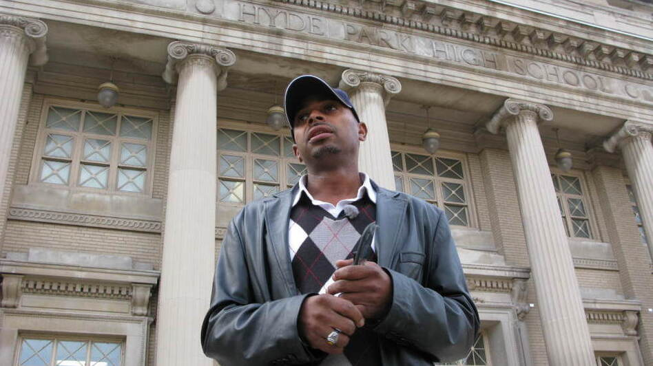 Herman Rainey, the Safe Passage coordinator for Leave No Veteran Behind, waits outside Chicago's Hyde Park Academy High School just before dismissal time. (NPR)