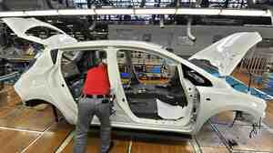 A worker assembles a Nissan Leaf electric vehicle at the company's Oppama plant in Yokosuka, Japan. Auto plants are reopening, but getting parts remains a challenge.
